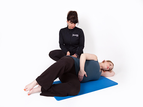 pregnant lady being taught pilates by teacher