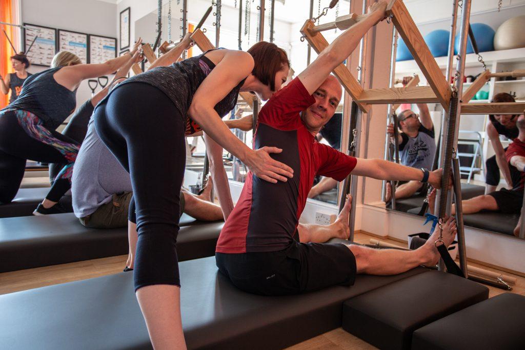 Teacher helping client in Tower Pilates