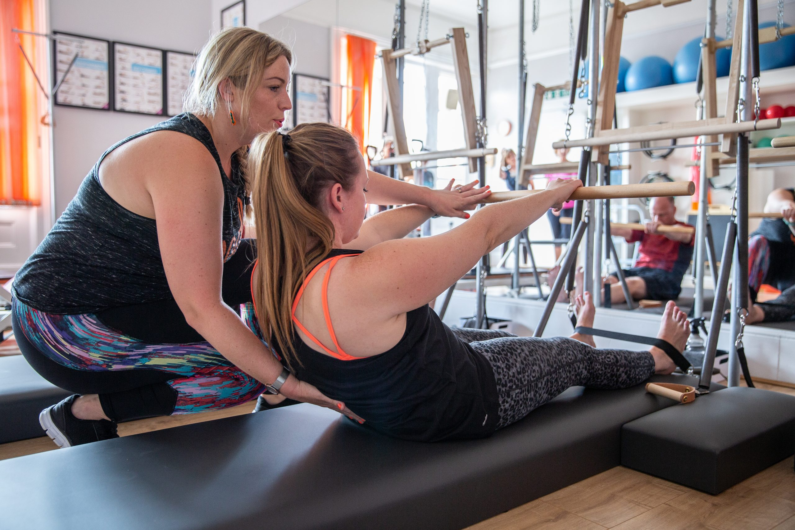 lady helping lady in pilates