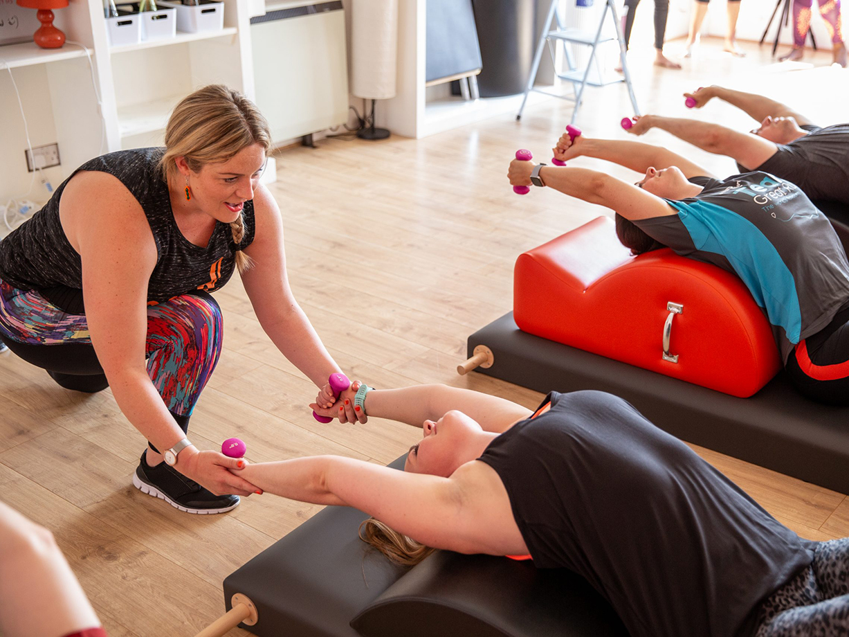 Pilates Instructor helping her clients