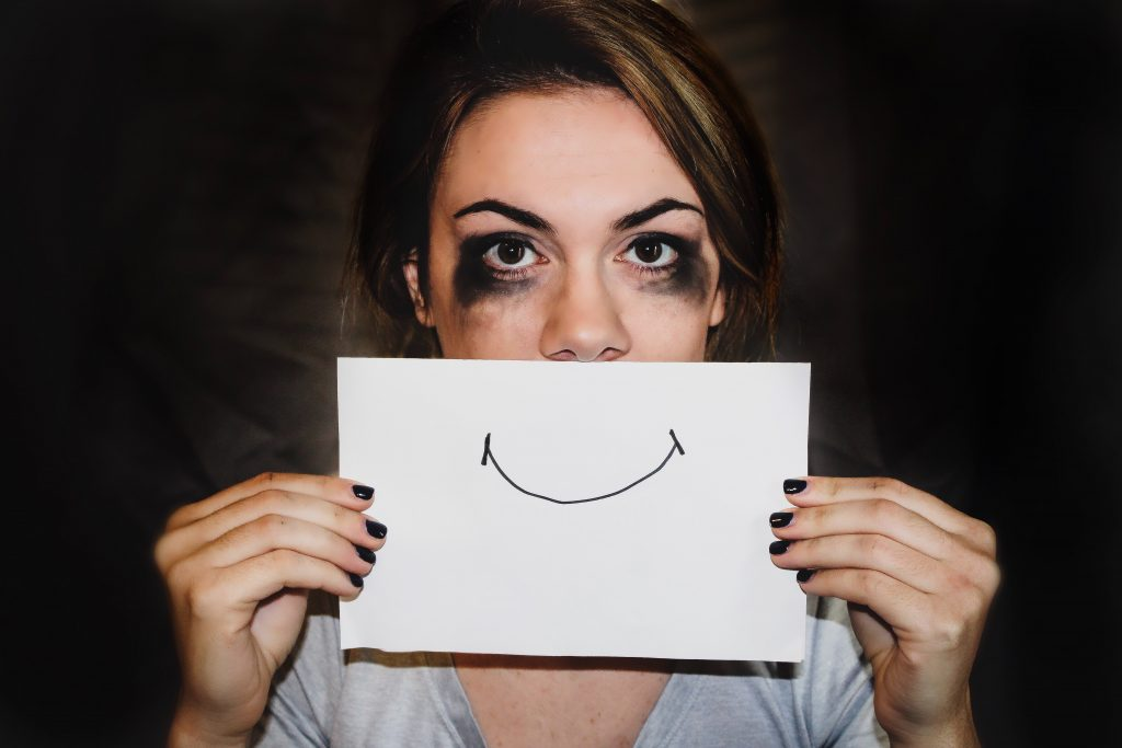 sad looking lady with smile picture over her face